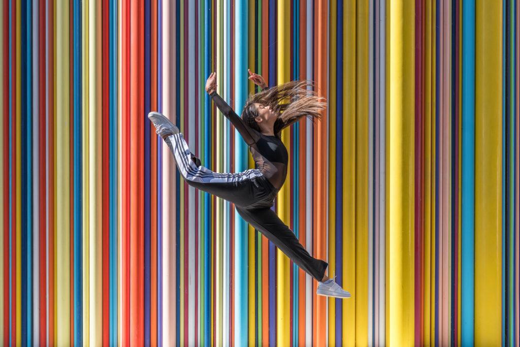 danseuse effectuant un saut devant le mur multicolor à courbevoie
