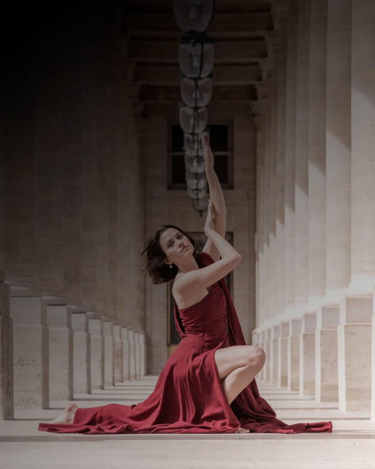 tirage vente danseuse avec une robe rouge entre les colonnes du palais royal à paris