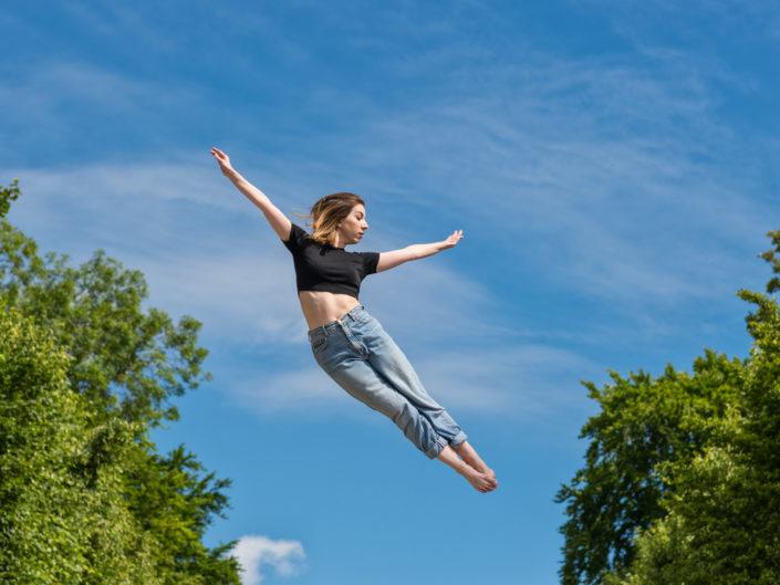 Danseuse effectuant un saut dans le parc de sceaux avec un beau ciel bleu