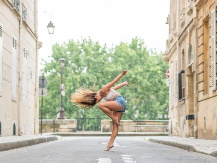 danseuse donnant du mouvement aux cheveux dans une rue parisienne sur l'ile saint louis