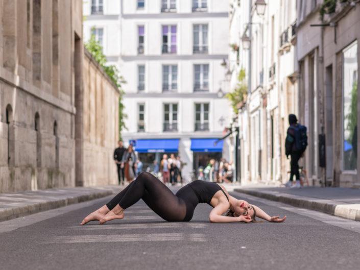 danseuse allongée en plein milieu d'une rue parisienne