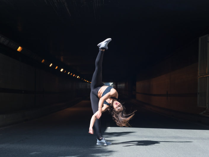 danseuse effactuant un jeté devant l'entrée d'un tunnel sur les berges à paris