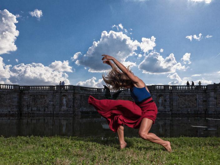 Danseuse justaucorps bleu jupe rouge en mouvement devant le chateau de fontainebleau