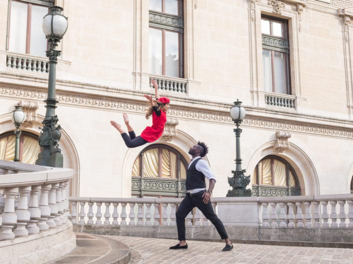 danseuse habillée en rouge effctuant un saut avec un danseur prêt à la réceptionner
