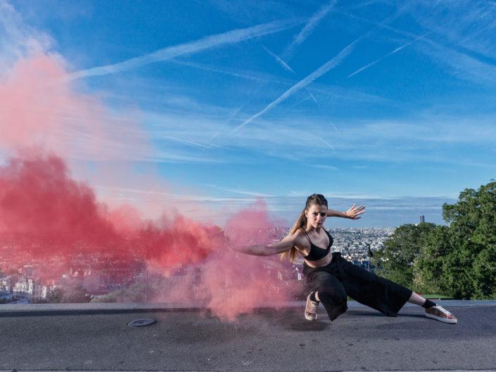 danseuse elodie leborgne avec un fumigene rouge en haut des marches de montmartre