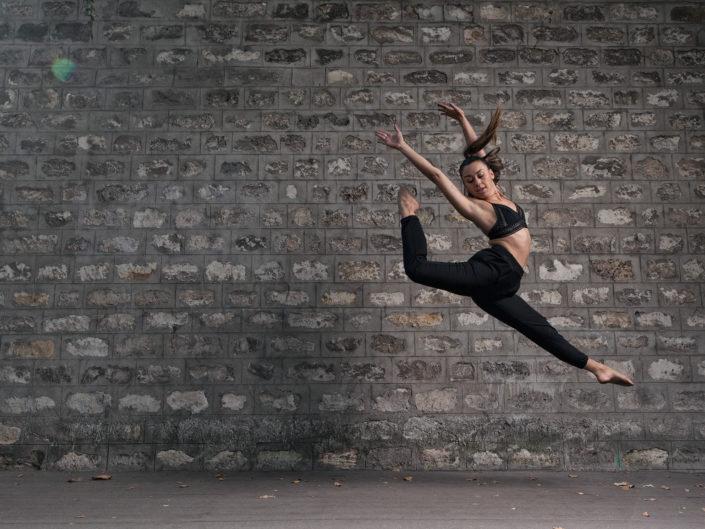 danseuse qui saute devant un mur de pierre vers la gare de bercy