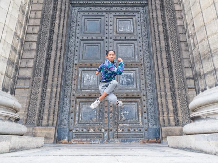 danseuse qui saute devant la grande porte de la madeleine