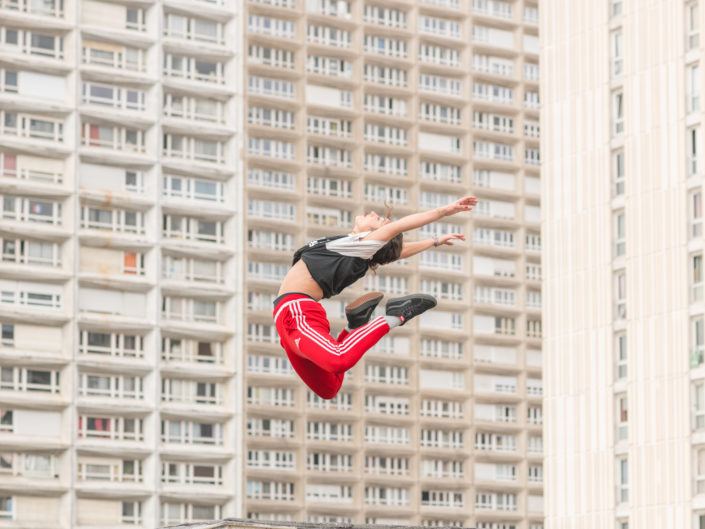 danseuse en levitation davant une barre de batiments