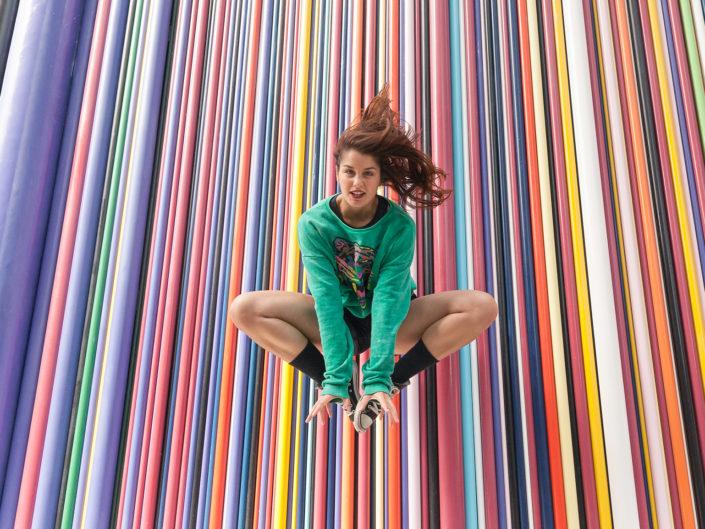 danseuse effectuant un saut devant un mur multicoloré à la défense en France