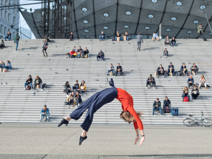 gymnaste effactuant un flip arriere devant arche de la defense