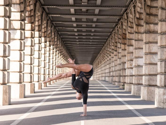 gymnaste effectuant un handstand sur le pont de becy