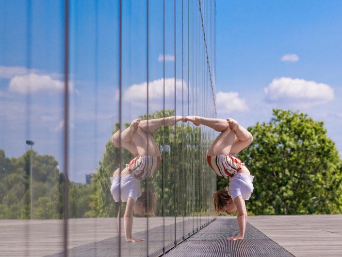 gymnaste lyonnaise effectuant un handstand contre une baie vitree de birhakeim