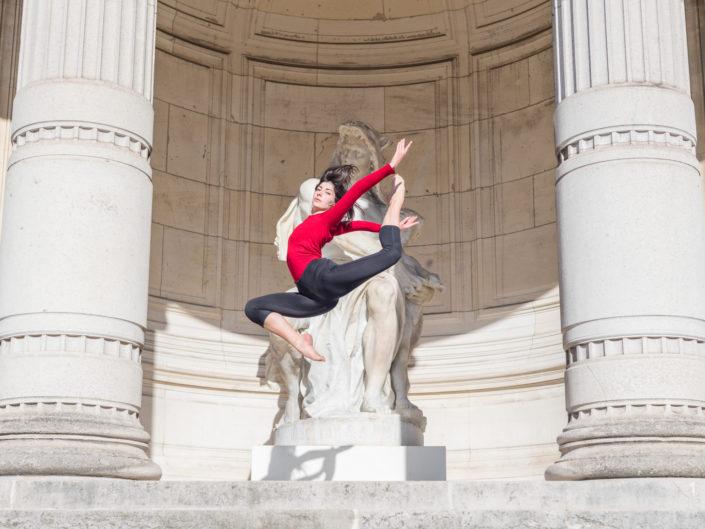 gymnaste faisant un saut avec un justaucorps rouge devant 2 colonnes